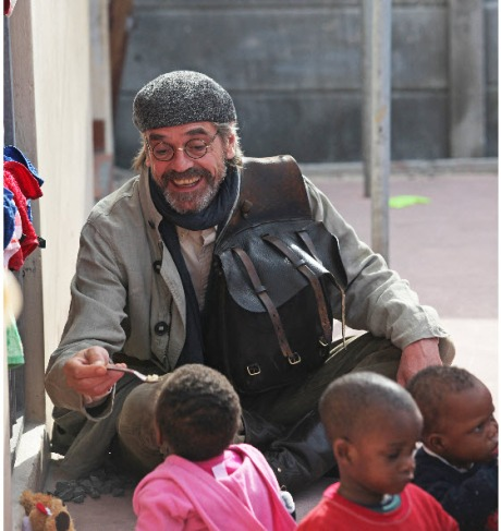 Jeremy Irons helps feed toddlers on the visit to Baphumelele Children's Home.